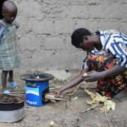 A woman in Rwanda feeds wood into a cookstove as a child looks on.