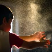 A child spraying something into the air by clapping.