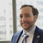 Sam Goodman in suit standing in front of windows