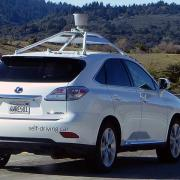 A Google self-driving car with lidar on top, cruising the interstate in California