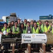 CU Hyperloop team members pose for a photo with their boring machine in Las Vegas