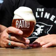 Hand holds a foamy glass of Ratio beer