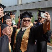Female engineering students pose for a selfie at graduation