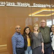 Srivastava, Waelde and friends pose beneath a new sign designating the lobby as the Srivastava-Waelde Engineering Lobby