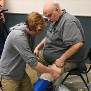 Max Armstrong helps an amputee put on his new prosthetic leg.