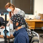 CU Boulder postdoctoral researcher Rosy Southwell and undergraduate student Cooper Steputis demonstrate the use of a functional near-infrared spectroscopy device, which can monitor brain activity.