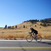 A woman rides her bike along a Boulder backroad.