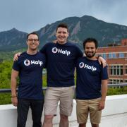 Fletcher Richman with Halp co-founders Tristan Rubadeau and Komran Rashidov on a balcony in Boulder with the Flatirons in the background.