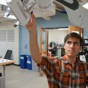 A student working with the robotic arm in the lab