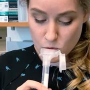 A researcher provides a saliva sample for a rapid COVID-19 test in a lab