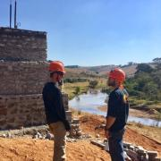 Two team members discuss construction near a bridge abutment in Swaziland.