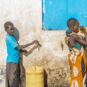 Two children fill water containers from a groundwater supply system in Turkana, Kenya