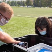 Cresten Mansfeldt and Katie Reeves examine a wastewater monitoring station that collects wastewater from the Kittredge residence hall complex.