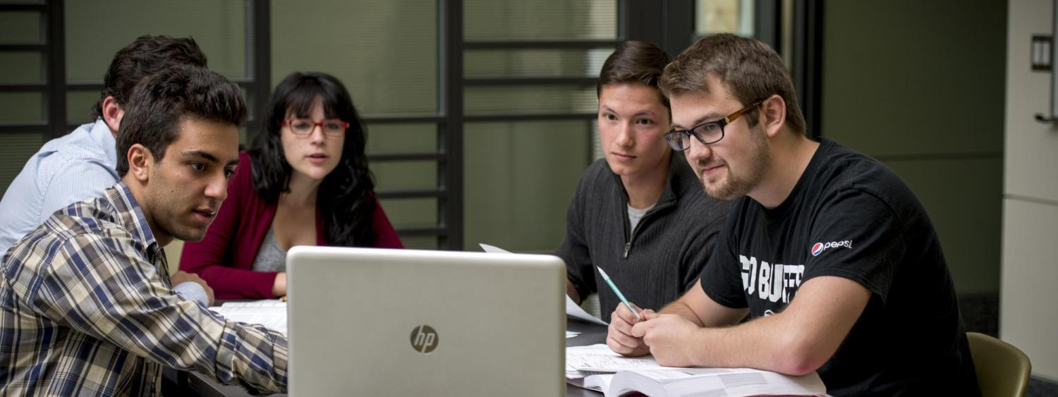 Five students sitting at a table looking at a computer