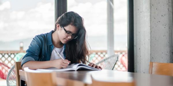 Female student studying at table with books