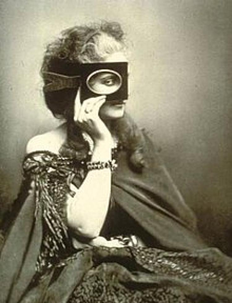 Photo of a woman in a dress covering her face with a mask