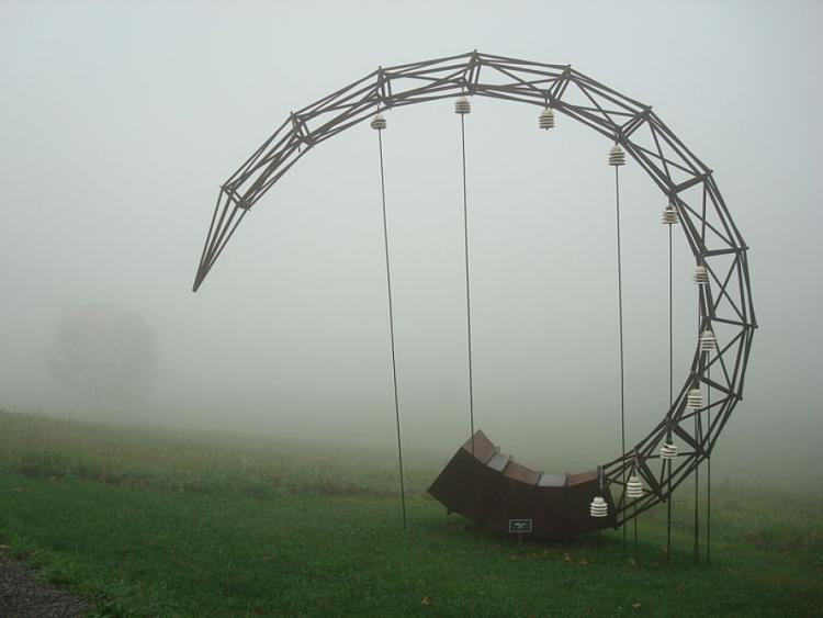 A horn-shaped wooden structure in a field