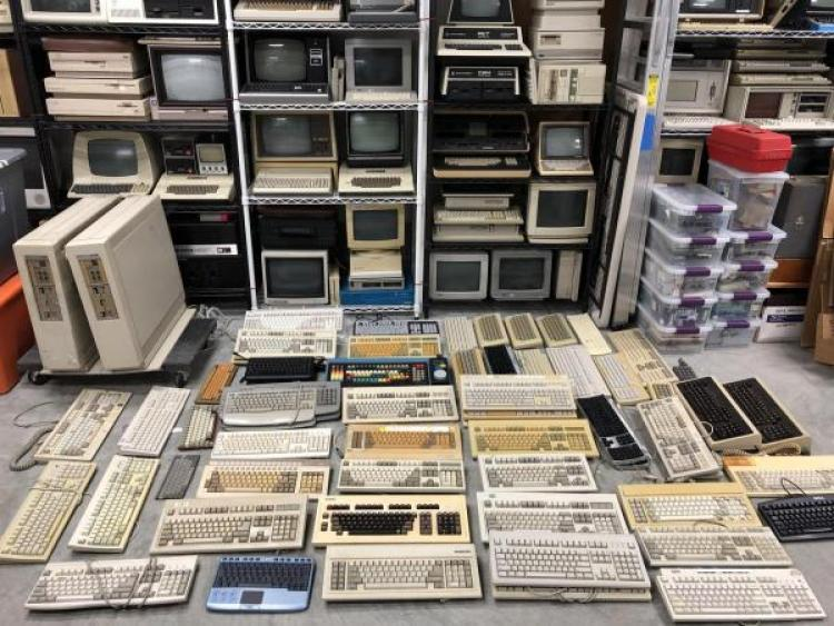 Stacks of computers and keyboards on shelves