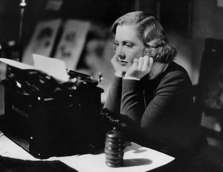 Woman at a desk with a typewriter looking frustrated