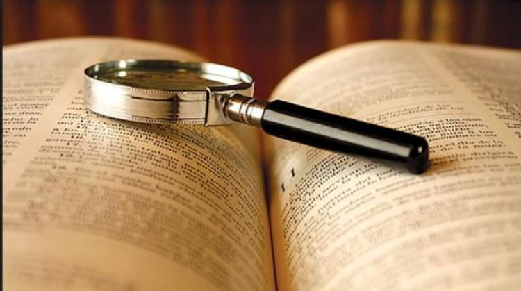 Open book with a magnifying glass on it