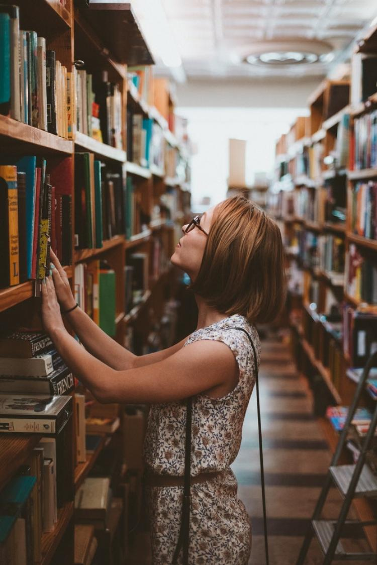 Woman picking a book from a bookshelf