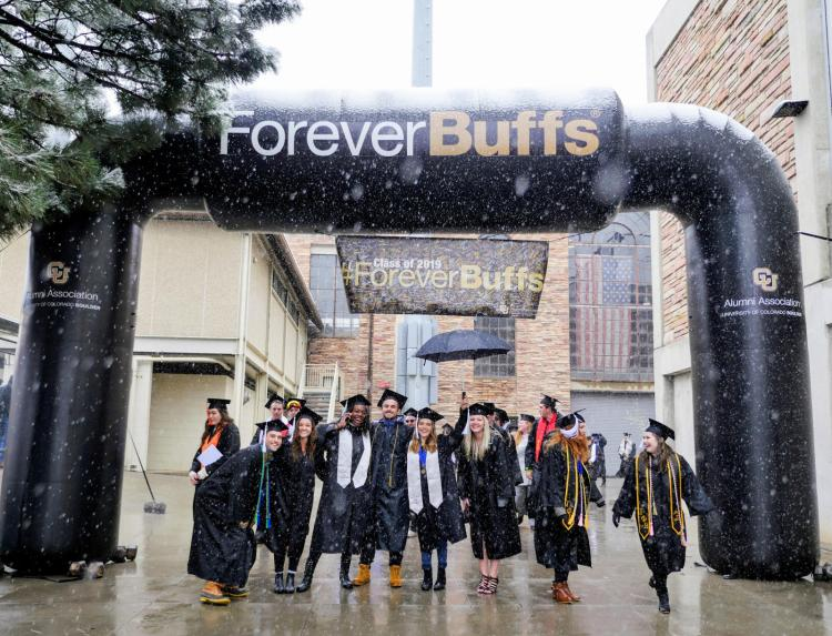 A group of CU graduates under a Forever Buffs insignia