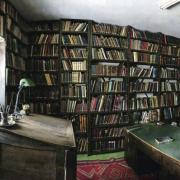 A room with a desk and stacks of books