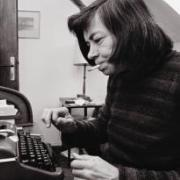 A woman is sitting at a desk in front of a typewriter