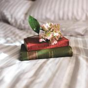 a pile of books on a bed topped by flowers