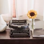 A typewriter on a desk next to flowers