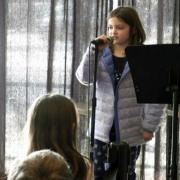 girl reciting poetry into microphone