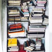 a bunch of books stacked in a stairwell