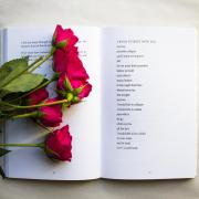 six roses on a book of poetry
