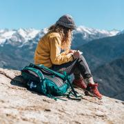 Woman writing in a notebook on top of a mountain