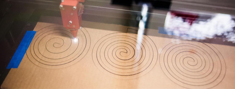 Laser cutter cutting spirals in cardboard.