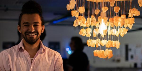 Zane Mitchell-Almoustapha with his digi-fab lamp, Sacral Chakra Chandelier