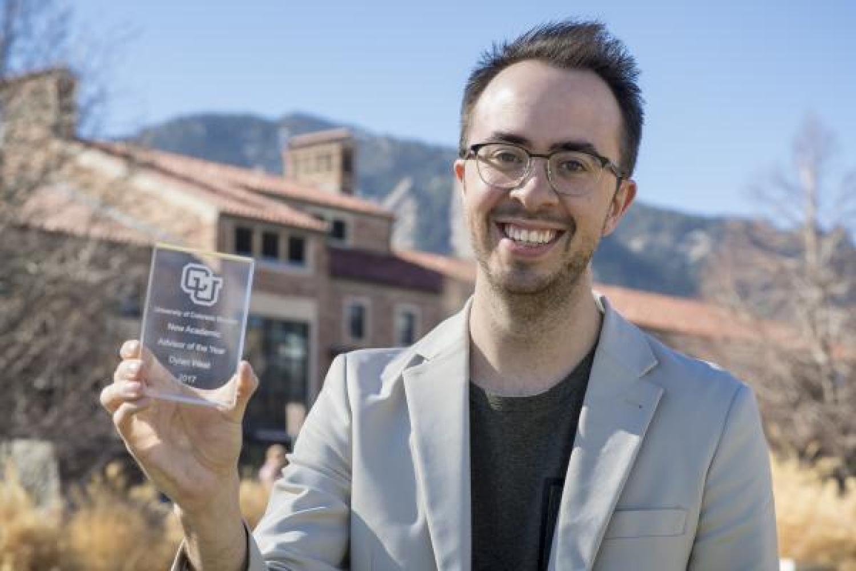 Dylan West holding his award for Outstanding New Advisor