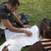 Assistant Professor, Alicia Gonzales and Kristina Lu view a map of Santiago