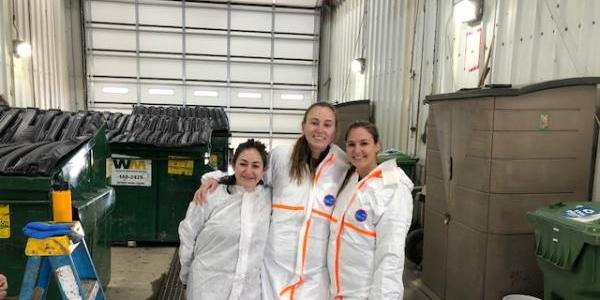 three students stand together auditing waste at vail