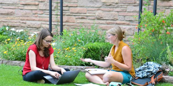 two students studying outside on the lawn