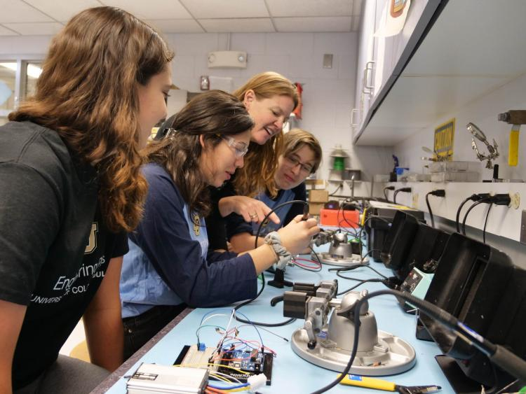 Dr. Z teaches soldering to group of female students