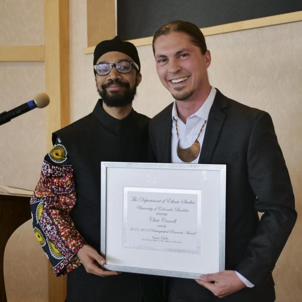 Dr. Clint Carroll receiving the Chair's Distinguished Research Award from Dr. Reiland Rabaka