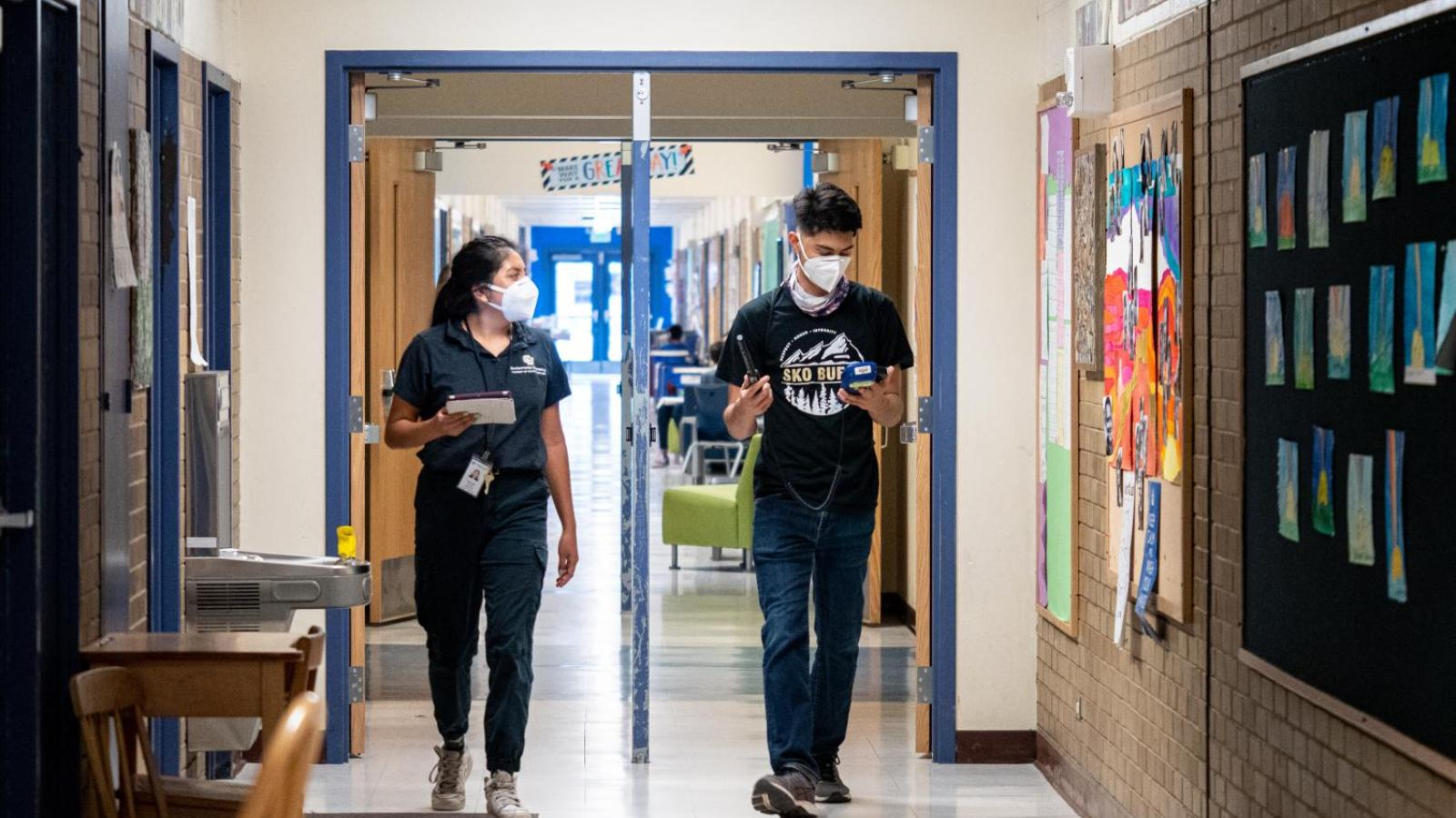 CU Boulder alumna Halle Sago, left, and undergraduate student Ricardo Reyes, right, visit High Peaks Elementary School in Boulder, Colorado, to monitor air quality.
