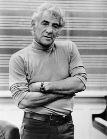Leonard Bernstein standing with arms folded