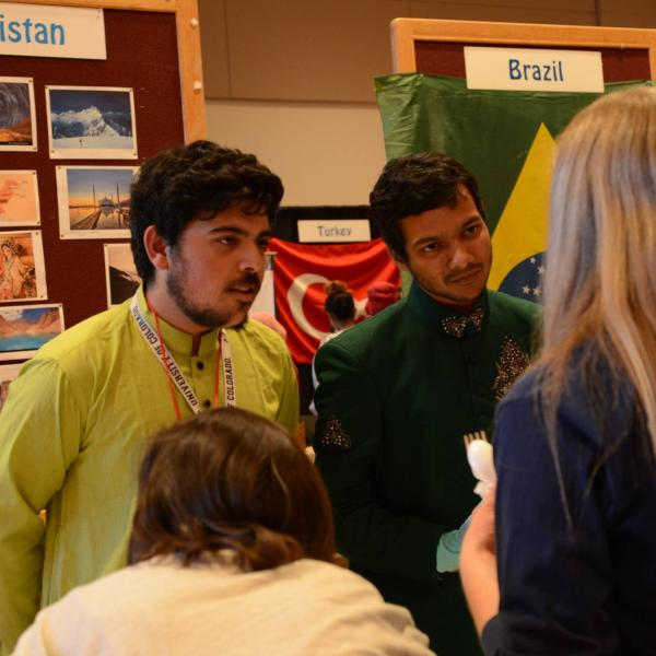 Two students from the Pakistan booth talking with some visitors at their booth.