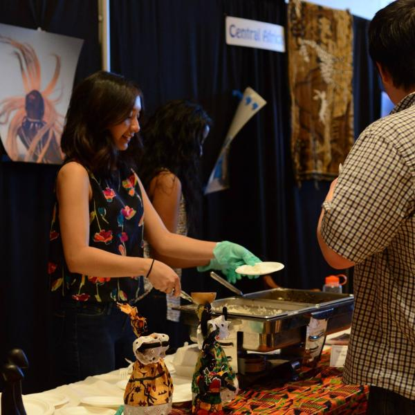 A student at the West Africa booth serving food for a visitor.