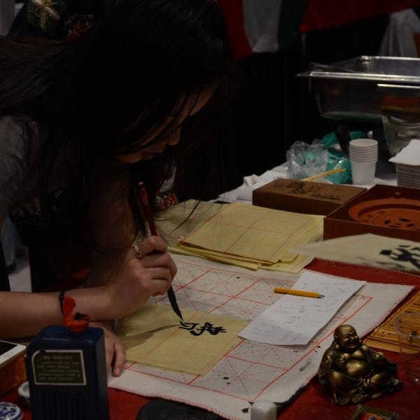 Student at Chinese booth doing Chinese manuscripts.