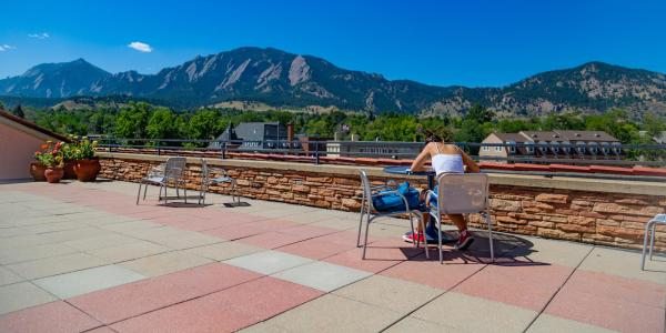 Student studying on UMC rooftop with Flatirons in the background