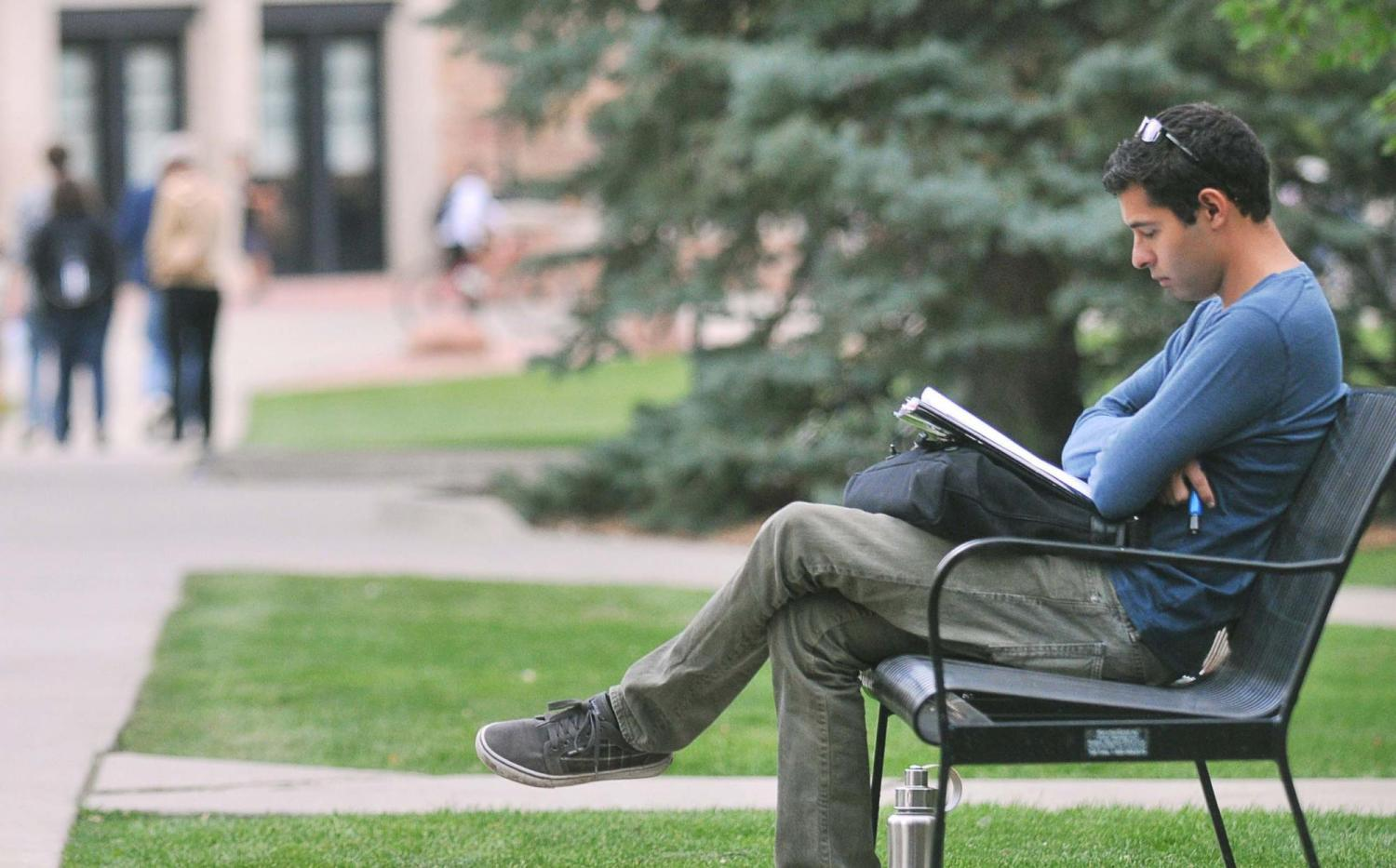Student sitting on bench in Norlin Quad reading