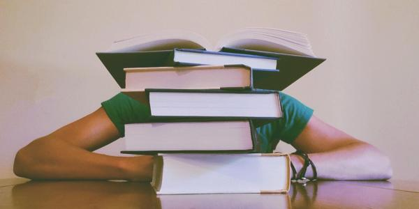 Student buries head behind pile of books